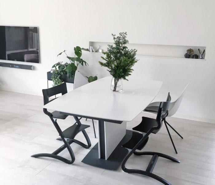 ダイニングテーブルとリースのための植物とフラワーベース